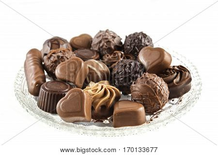 Chocolate pralines assortment on a glass plate isolated against a white background selected focus narrow depth of field