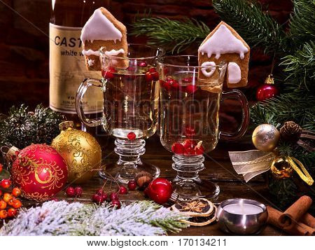 Two glasses with hot tea, decorated with Christmas cookies. Snow-covered fir branch on a wooden table, Christmas balls.