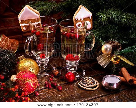 Beautiful Christmas still-life from two glasses of hot punch and surrounded by fir branches and Christmas balls.