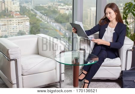 Young asian business woman in suit looking at the chart on the sheet sitting in an easy chair in the office