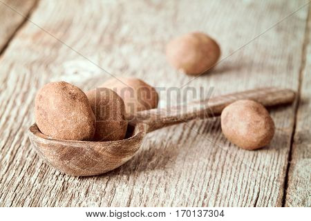 Spoon with chocolate balls on wooden background
