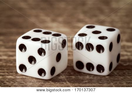 Two dice on dark wooden table background. Gambling concept.