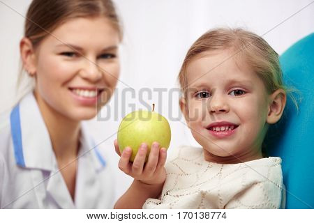 Cute girl holding green apple, sitting on chair in dental clinic. Concept of teeth cure and regular checkup.