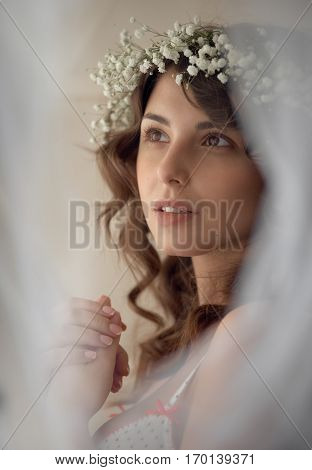 Portrait of sensual woman in circlet of flowers looking at camera