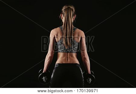 Cross fit woman holding dumbbells standing over dark background. Concept of bodybuilding, weightlifting and training.