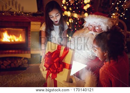 Santa Claus with little girls opens a box with Christmas magic