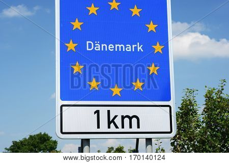 Photo with Danish border sign by the road.