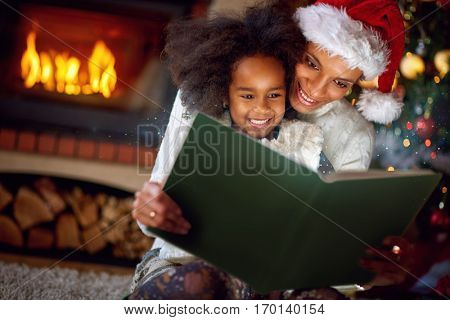 Adorable little girl reading fairytales with mom on Christmas evening