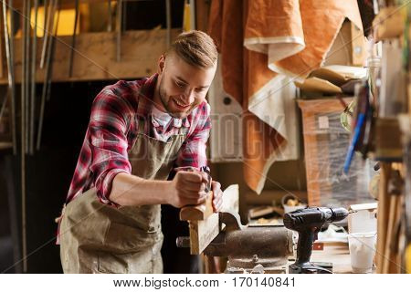 profession, people, carpentry, woodwork and people concept - happy carpenter with jointer planing wood plank at workshop poster