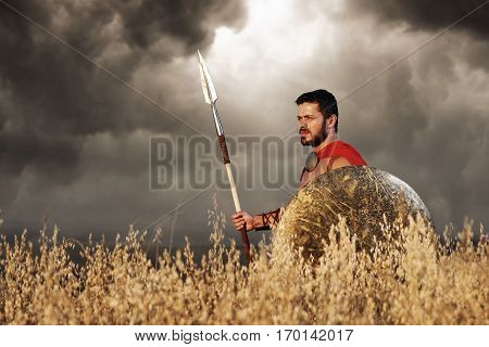 Warrior with beard in armor like antique roman looking away, going in attack at field. Side view of soldier wearing in red cloak like spartan holding bronze sword. Dark sky and bad weather.
