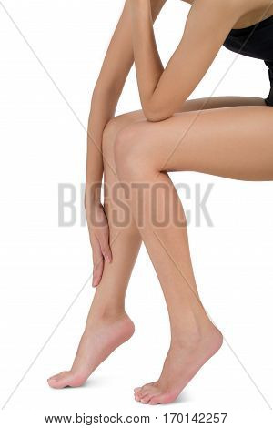 woman sitting and holding her beautiful Healthy long leg with massaging shin in pain area Isolated on white background.