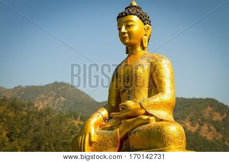 Golden Statue of Budhda with background of green forest and blue sky.