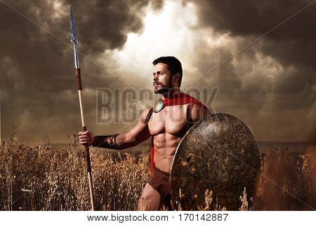 Athletic warrior with beard wearing like spartan looking away and holding iron weapon in hand. Brunet soldier with bare torso in red cloack going in attack with rounded shield and weapon. War in field.