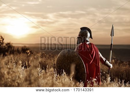 Back view of warrior man wearing iron helmet and red cloak holding sword, soldier looking and turned back. Male wearing like spartan or antique roman at field on sunset.