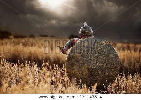 Confident incognito warrior going forward in attack with bronze rounded shield. Soldier in armor and helmet like spartan holding weapon front of himself. Dark clouds in sky. War in field.