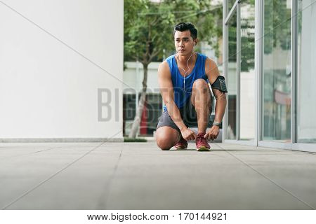 Portrait of young Asian sportsman listening to music in headphones while tying his shoelaces before morning run