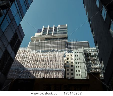 HONG KONG - October 2016: Street view with modern building covered in bamboo scaffolding and white fabric.
