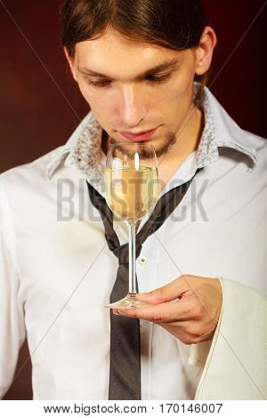 Winery alcohol liquor drinking concept. Somellier checking wine quality. Young male waiter holds wine glass.