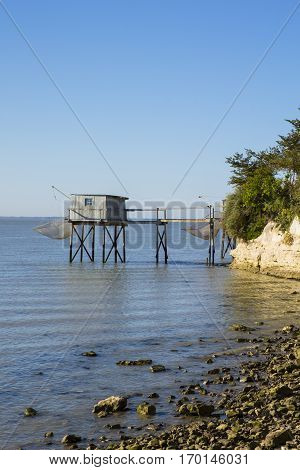 traditional fisherman's wooden hut at the bottom of the limestone cliff in the estuary of Gironde Talmont