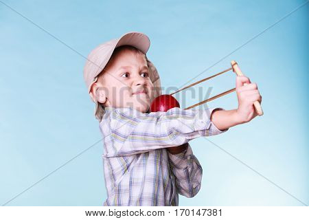 Nature and free time prankster little boy. Child have fun with wooden sling shot and fruit aim apple.