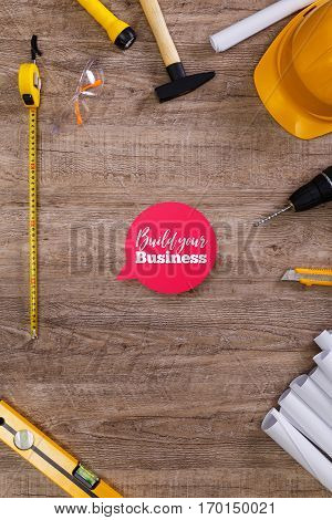 Helmet, flashlight and tape measure. Build your business speech bubble. Paper plans, knife and protective glasses. Building level, hammer.