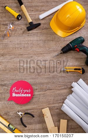 Helmet, flashlight and hammer. Build your business speech bubble. Architecture plans, knife and protective glasses. Building level and drill.