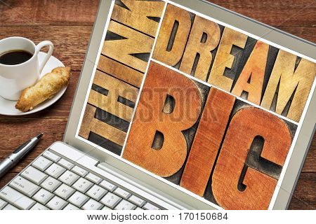 think and dream big motivational phrase -  word abstract in letterpress wood type printing blocks on a laptop screen with coffee