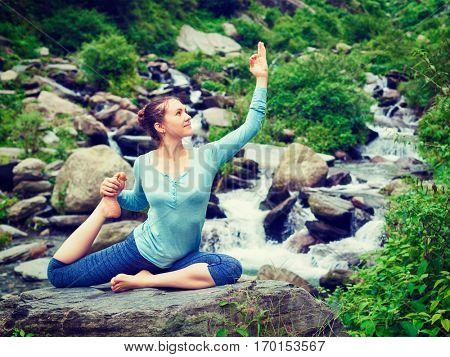 Young sporty fit woman doing yoga asana Eka pada rajakapotasana - one-legged king pigeon pose at tropical waterfall. Himachal Pradesh, India. Vintage retro effect filtered hipster style image.
