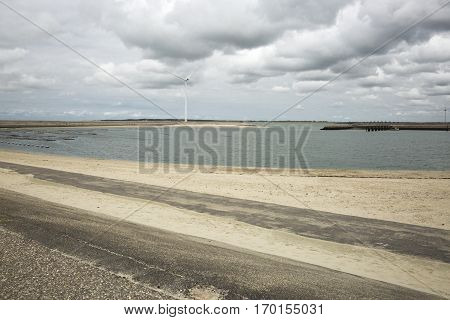 Seaside view with power windmills, a dike and dramatic sky, Haringvliet, The Netherlands