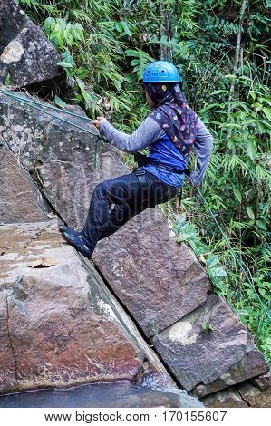 Beaufort,Sabah,Malaysia-Jan 28,2017:Muslim girl with scarf rappelling in Jempangah waterfall at Beaufort,Sabah,Borneo.Waterfall Abseiling activity adventure getting famous in Sabah,Borneo,Malaysia
