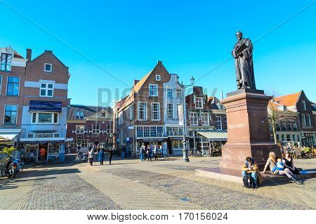 Delft, Netherlands - April 8, 2016: Statue of Hugo Grotius, traditional dutch houses, people in downtown of popular Holland destination