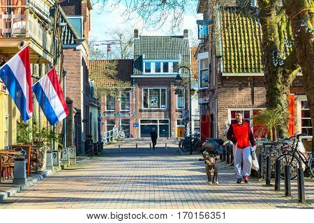 Delft, Netherlands - April 8, 2016: Colorful street view, dutch houses and people in Delft, Holland