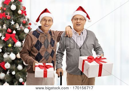 Cheerful seniors with presents in front of a christmas tree isolated on white background