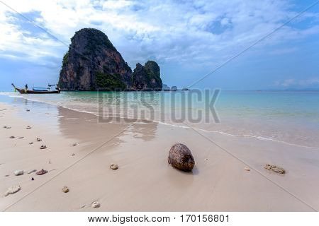 Sunset at Phra Nang Beach, Krabi, Thailand. Typical boat Longtail on a background of smoky islands - rocks and sea in sunset colors