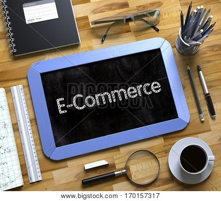 E-Commerce - Text on Small Chalkboard.E-Commerce Handwritten on Blue Small Chalkboard. Top View of Wooden Office Desk with a Lot of Business and Office Supplies on It. 3d Rendering.