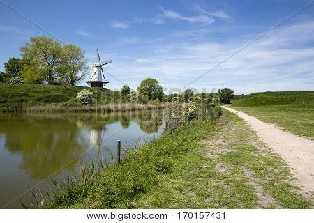 Typical Dutch landscape with a canal and a windmill, Molen de Koe, Veere, The Netherlands