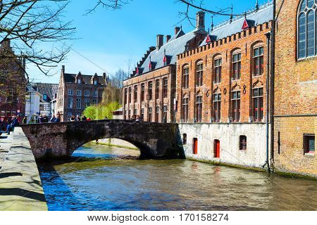 Bruges, Belgium - April 10, 2016: Scenic cityscape with houses, people on bridge and canal in Bruges, Belgium
