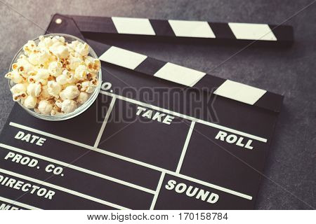 popcorn and movie maker on black table background