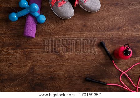 Fitness gym equipment. Sneakers, dumbbells with towel and skipping rope. Workout footwear and drink. Sport trainers on grunge rustic wood background.