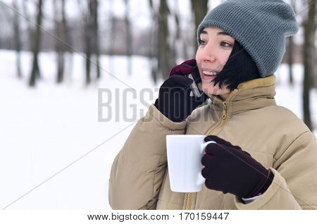 Winter Portrait Of Young Girl With Smartphone And Coffee Cup