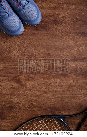 Fitness gym equipment. Tennis racquet and Sneakers. Workout sport footwear. Grunge rustic wood background.