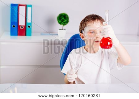 Boy Mixing Colored Liquids In Test Tubes