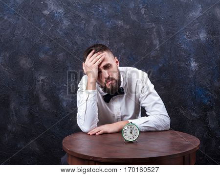young bearded man holding his head alarm