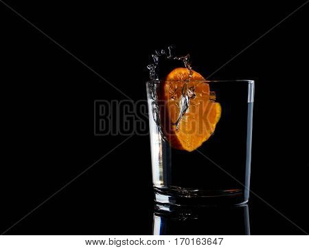 Water in glass with water splash with tangerine energy clear