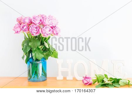 Violet rose bouquet with letters home on wooden shelf