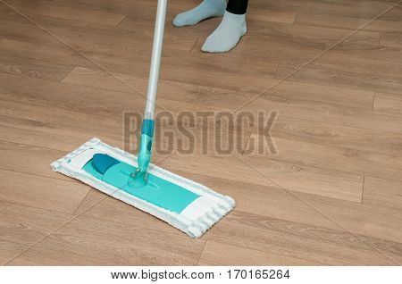 Close up of woman legs with mop cleaning floor at home