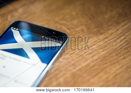 Smartphone On Wooden Background With 5G Network Sign 25 Per Cent Charge And Scotland Flag On The Scr