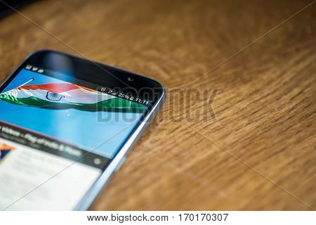 Smartphone On Wooden Background With 5G Network Sign 25 Per Cent Charge And India Flag On The Screen