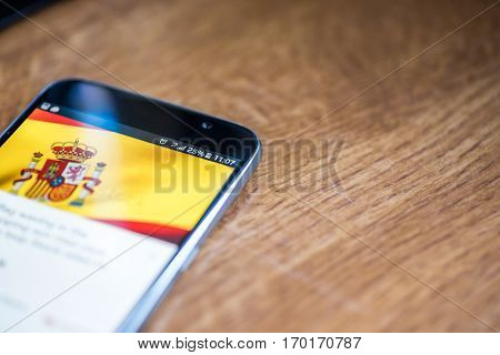 Smartphone On Wooden Background With 5G Network Sign 25 Per Cent Charge And Spain Flag On The Screen