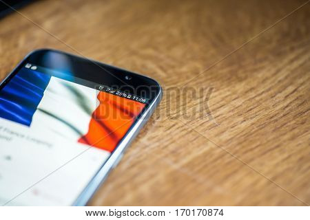 Smartphone On Wooden Background With 5G Network Sign 25 Per Cent Charge And France Flag On The Scree